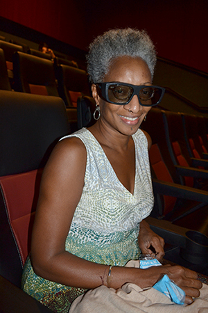 Cynthia Oliver, Associate Vice Chancellor for Research in the Humanities, Arts, and Related Fields, dons her 3D glasses in preparation for watching <em>A Beautiful Planet</em>.