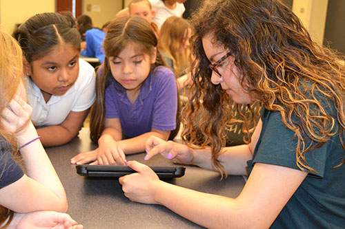 Lina Flores helps IPA 3rd graders program their Dash robot.