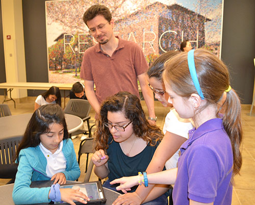 Yann Chemla (center back) watches Lina Flores teach IPA students how to program their Dash robot.