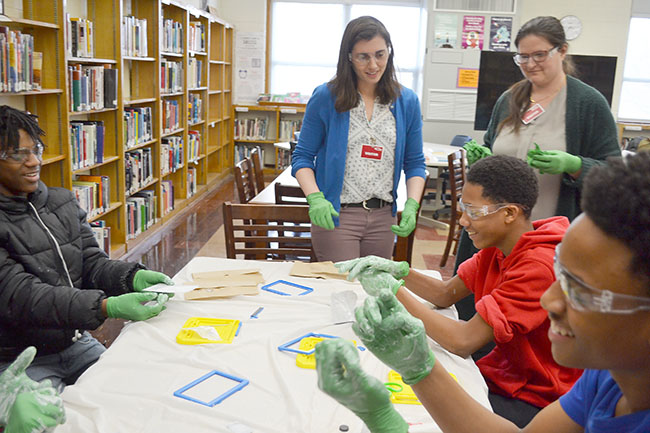 "Maggie Mahmood and Pamela Pena Martin (standing) interact with Franklin students who have finished ""destroying"" their Magnadoodles."