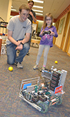 Robotics members teach a local youngster how to operate a robot they brought to the event.
