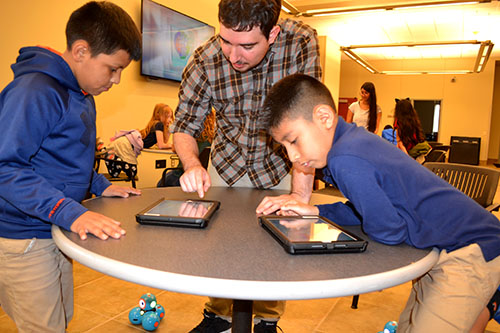 Andres Arango (center) interacts with students who are programming their Dash Robot.