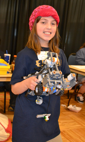 Youngster proudly displays the robot she helped build for the 4-H Robotics competition.