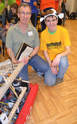 4-H Robotics Educator Bob Smith and a participant in the 2013 Robotics Competition pose by a robot.