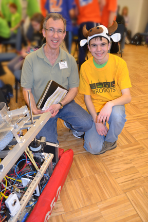 Bob Smith and 4-H robotics competitor pose by a robot.