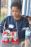 A high school participant works on her team's catapault as part of the design challenge.
