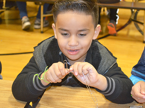 A young Cena y Ciencias visitor works on putting together their paper clip chain.