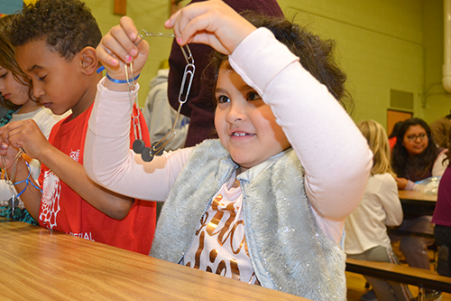 A young Cena y Ciencias visitor with their paper clip chain.