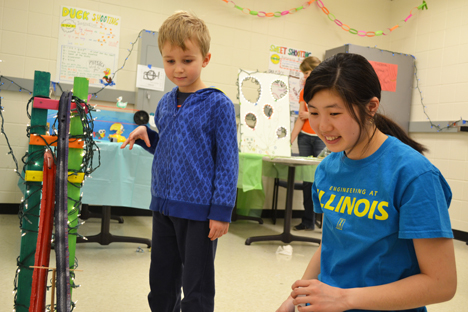 Illinois student Kaylin Moy does a Physics Coaster exhibit with a youngster. While playing, he learned a bit about potential energy, kinetic energy, and friction.