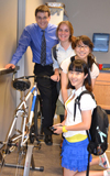 Power House team poses by the prototype of their power-generating stationary bicycle.