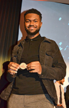 Amaury Saulsberry, a member of the winning team who dreamed up Nouvou, the Smart Pacifier, shows off their prize, a
