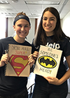 SWE members Taylor Wills and Dionora Osmani hold notebooks they made out of one-sided recycled white paper, complete with a cereal box or cardstock cover, which they decorated themselves, as part of SWE's Project Paplet. (Image courtesy of Berat Gulecyuz.)