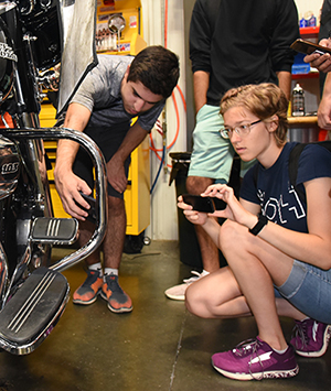 Students check out a Harley Davidson motorcycle.