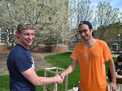 Sameh Tawfick (right), shakes hands with the ME370 student who successfully dunked him.
