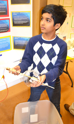 Next Gen sixth grader illustrates part of his team's hydropower design.