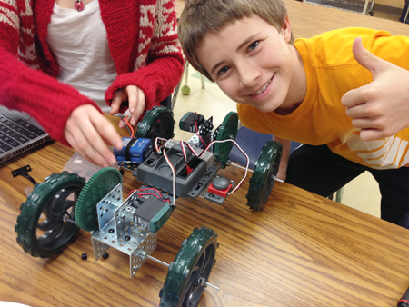 Eighth grader proudly displays robot he helped build during Fritz's Project Lead the Way unit.