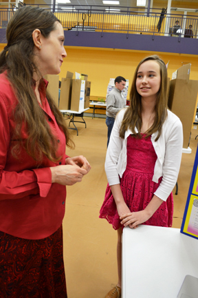 Science Fair coordinator Carrie Kouadio discusses Next Gen student's project with her.
