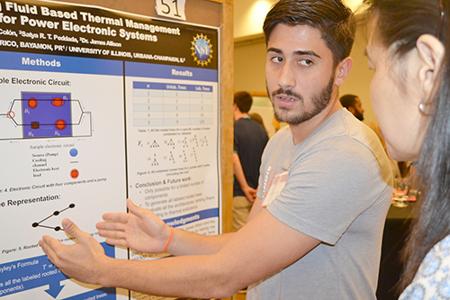 POETS REU participant Ian Rivera-Colon explains his study to a visitor at the Illinois Summer Research Symposium.
