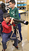 Student looks through a telescope