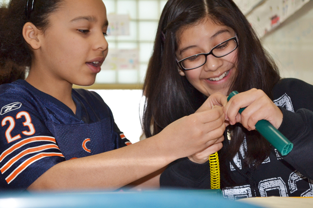 Two edison middle school girls work together to create a model of their design.
