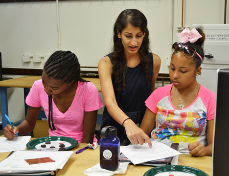 Parul Koul (center) works with a GLAM camper during the session on analyzing chocolate.