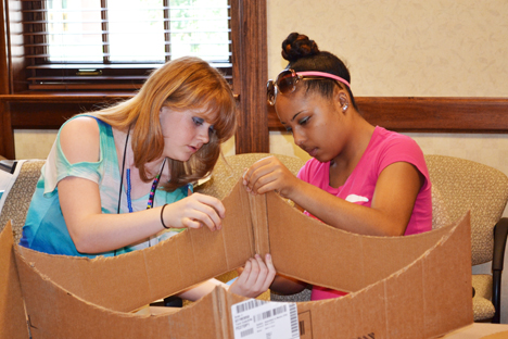 Two campers work during a hands-on project during which campers made solar ovens.