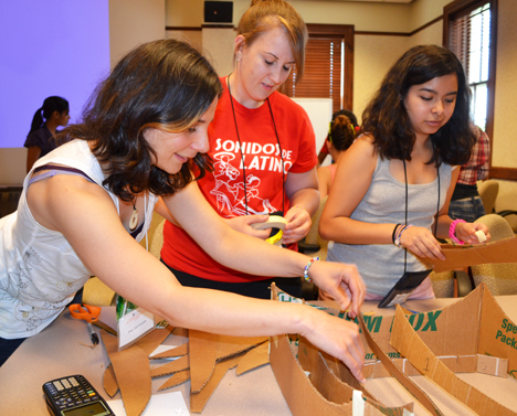 Elif Ertekin (left) lends a hand to a couple of campers during the solar oven session.