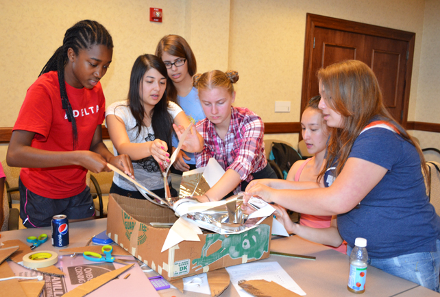 Group of campers from a joint session of GLAM and G-BAM assemble the framework for the solar oven they were collaborating on.