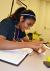 Camper uses a ph strip to test a water sample during a hands-on activity exploring water purity.
