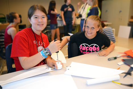 Two campers assemble their wind turbine.