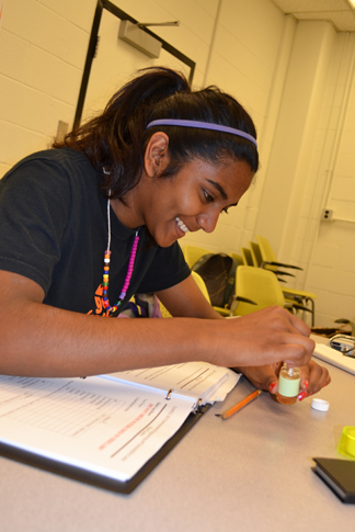 G.A.M.E.S. camper in the Environmental Engineering and Sustainability camp tests the purity of a water sample.