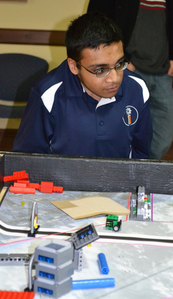 iRobotics Outreach Coordinator Arsalan Aslam watches a team go through a practice run at the practice tournament he organized.