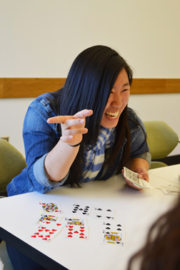 Eileen Ryu enjoying an interaction with a middle school student while playing a math-based card trick at iMATHS.