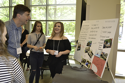 MechSE's Joe Muskin (upper left) looks on as a Centennial student as she explains about her team's research during the IRISE 2017 Symposium held last spring