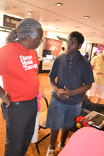DJ Jackson (right), Centennial sophomore, interacts with a visitor at the Pygmalion Festival