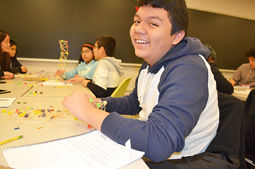 A ChiS&E seventh grader enjoys making his team's toothpick-gumdrop structure.