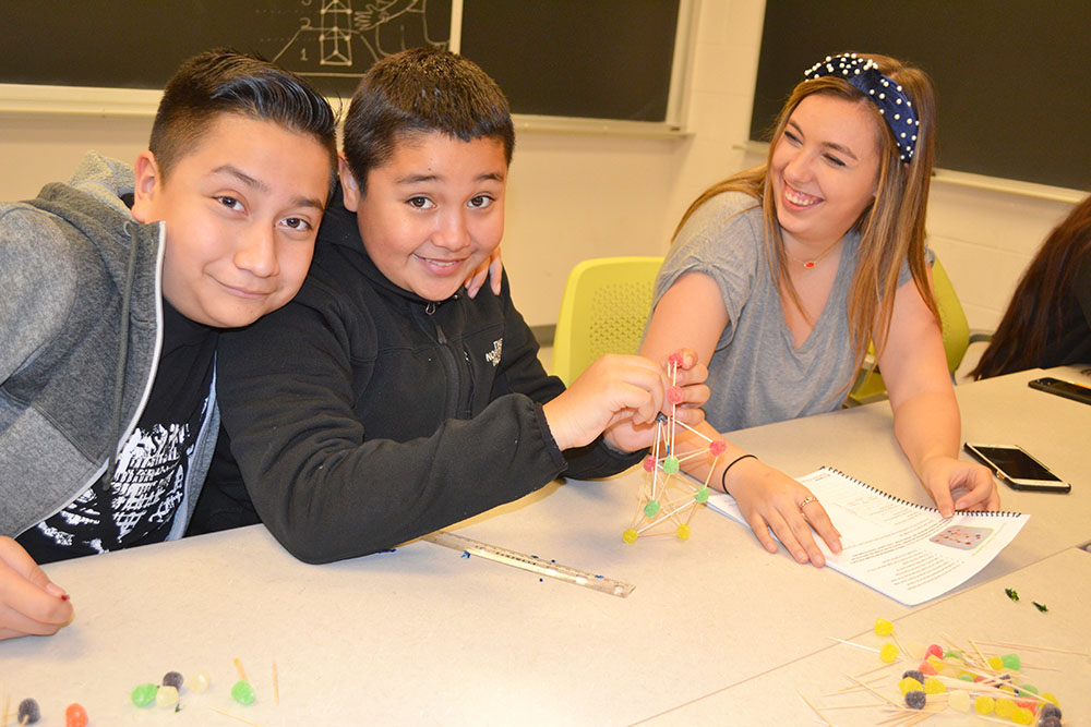 ChiS&E seventh graders work on a toothpick-gumdrop structure.