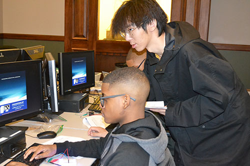 An Illinois engineering student (right)  works with a Chicago eighth grader during the Computer Science activity.