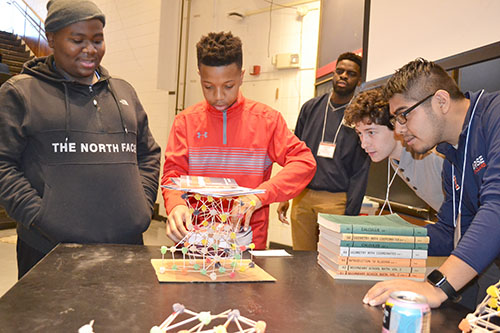 llinois engineering students (right) watch as two Chicago seventh graders test their structure by piling books on it.