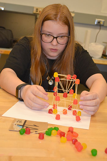 A  Mid-GLAM camper works on her team's toothpick/gumdrop structure.