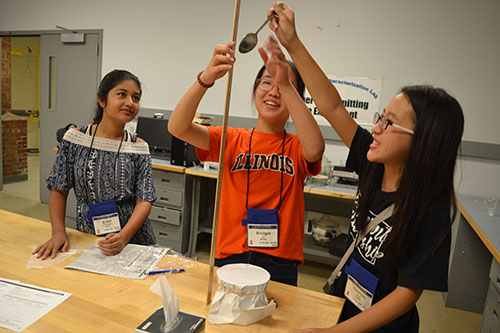 A team of campers test the strength of freezer paper by dropping a spoon on it. They found it to be the strongest of the various materials