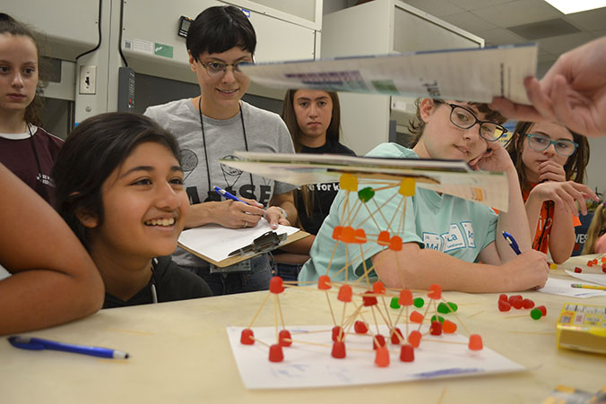 Mid-GLAM campers and lab assistants watch as journals are piled on one team's structure during testing.