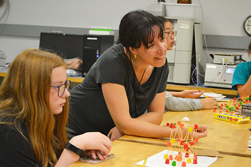 Ceclia Leal (center) ejoys watching a team's toothpick/gumdrop structure being tested.