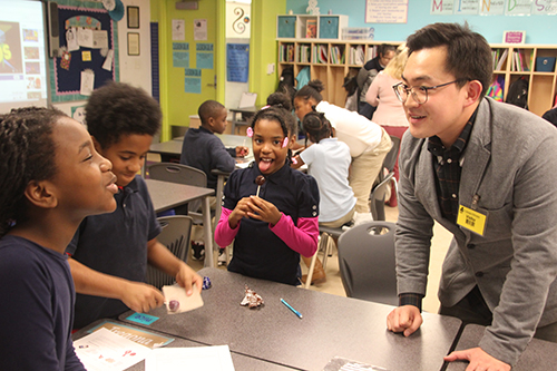 Jiho Kim interacts with BTW fourth graders as the students either rub their suckers on sandpaper and/or lick them as part of his corrosive wear activity. (Photo courtesy of Joe Muskin.)