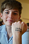 A Blue Waters intern displays the tatoo she got during a tour of the Petascale facility. The message: Live free; code hard