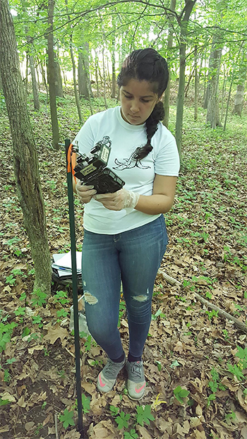 Alondra Estrada setting up a camera out in the woods where she studied turtles.