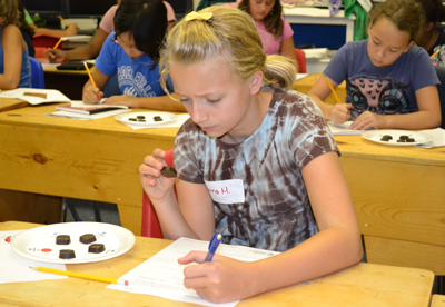 GIRRRLS camper examines bloom on chocolate during hands-on activity.