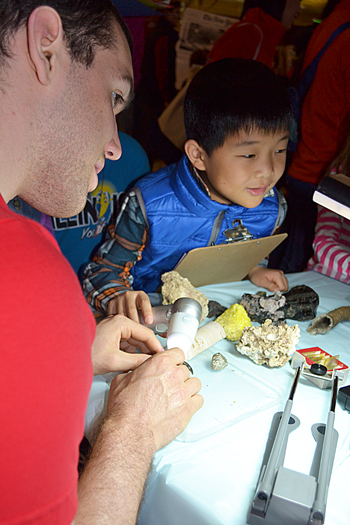 Jim Bruce supervises while a local youngster uses the ProScope to magnify rocks and coral.
