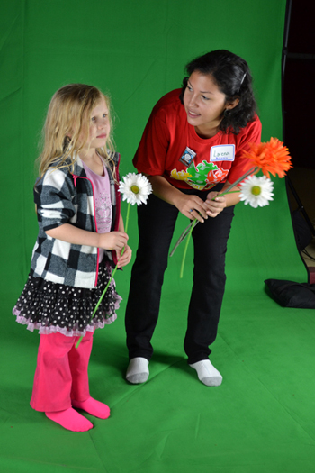 "Local youngster and Illinois graduate student stand in front of a green screen so they can ""dance with plants."""