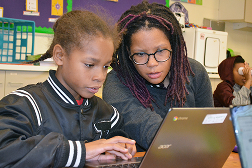 King's Shalonda Carr works with a student who is using TinkerCAD to design a keychain.
